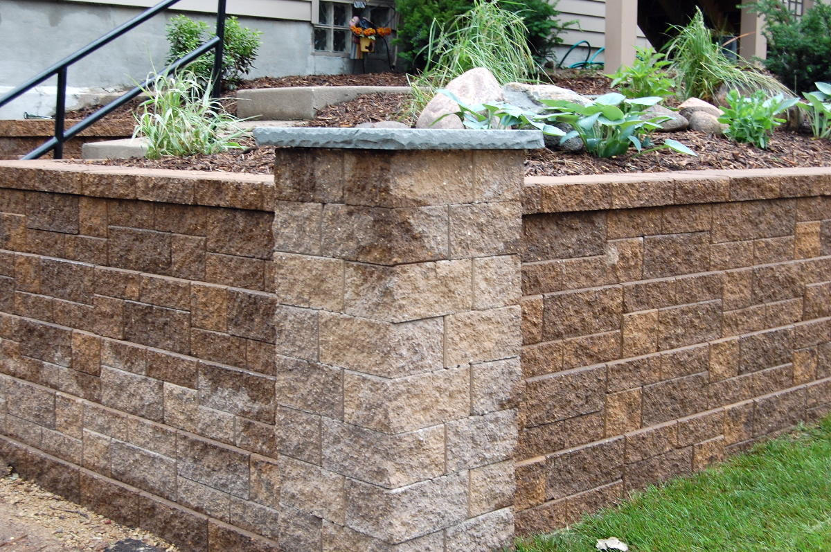 <b>Chestnut Blend block and caps, Bluestone column caps</b> VERSA-LOK Standard<br /><b>Color:</b> Chestnut Blend block and Tan caps<br /><b>Style:</b> Mosaic retaining wall with columns<br /><b>Location:</b>  Corner of Cunty Rd. B and Western Ave.<br /><b>Install Date:</b> June 2010