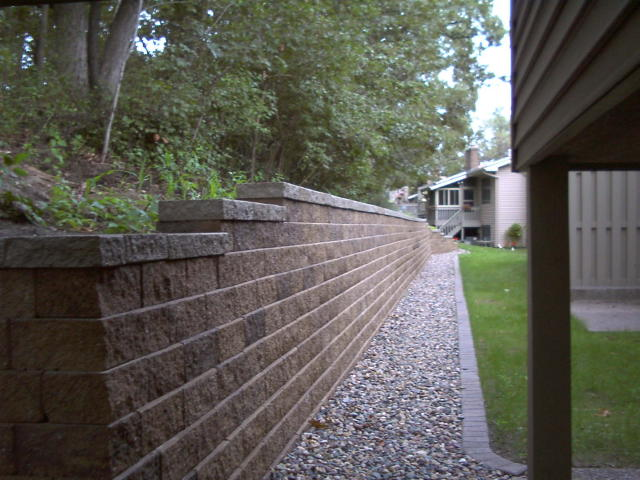 <b>Retaining wall</b> VERSA-LOK<br /><b>Color:</b> Chestnut Blend block with Grey caps<br /><b>Style:</b> Replacing timber wall; 3/4 setback; 45 degree corners<br /><b>Location:</b> Sterling and Mailand South Maplewood<br /><b>Install Date:</b> April 2006