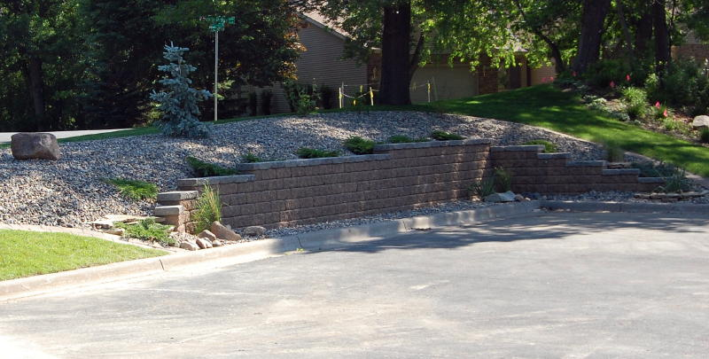 <b>Retaining wall</b> VERSA-LOK Weathered<br /><b>Color:</b> Chestnut Blend block / Charcoal caps<br /><b>Style:</b> Replacing timber wall; 3/4 setback; 45 degree corners<br /><b>Location:</b> Sterling and Deer Ridge Ct. South Maplewood<br /><b>Install Date:</b> May 2009