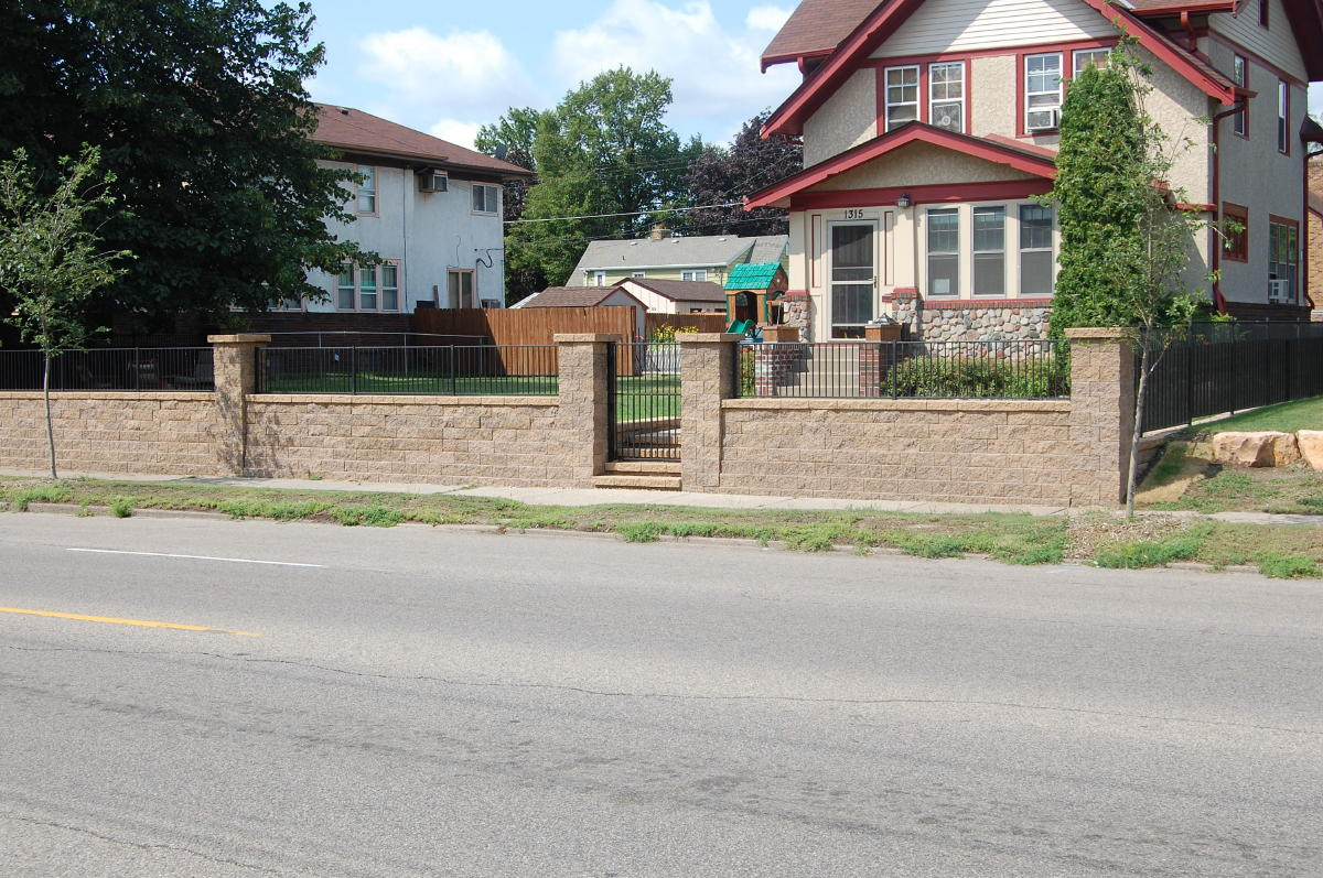<b>Free Standing Walls and Columns</b> VERSA-LOK Standard<br /><b>Color:</b> Chestnut Blend block with Tan caps<br /><b>Style:</b> Free standing walls built atop retaining wall, Iron fence to top of columns<br /><b>Location:</b>  Corner of Dale and Wheelock<br /><b>Install Date:</b> June 2009