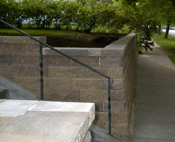 <b>Retaining wall</b> VERSA-LOK<br /><b>Color:</b> Chestnut Blend block with matching caps<br /><b>Style:</b> 3/4 setback; 90 degree corners; Step sidewalls<br /><b>Location:</b> Near Lincoln and Lexington Titusville, FL<br /><b>Install Date:</b>June 2002